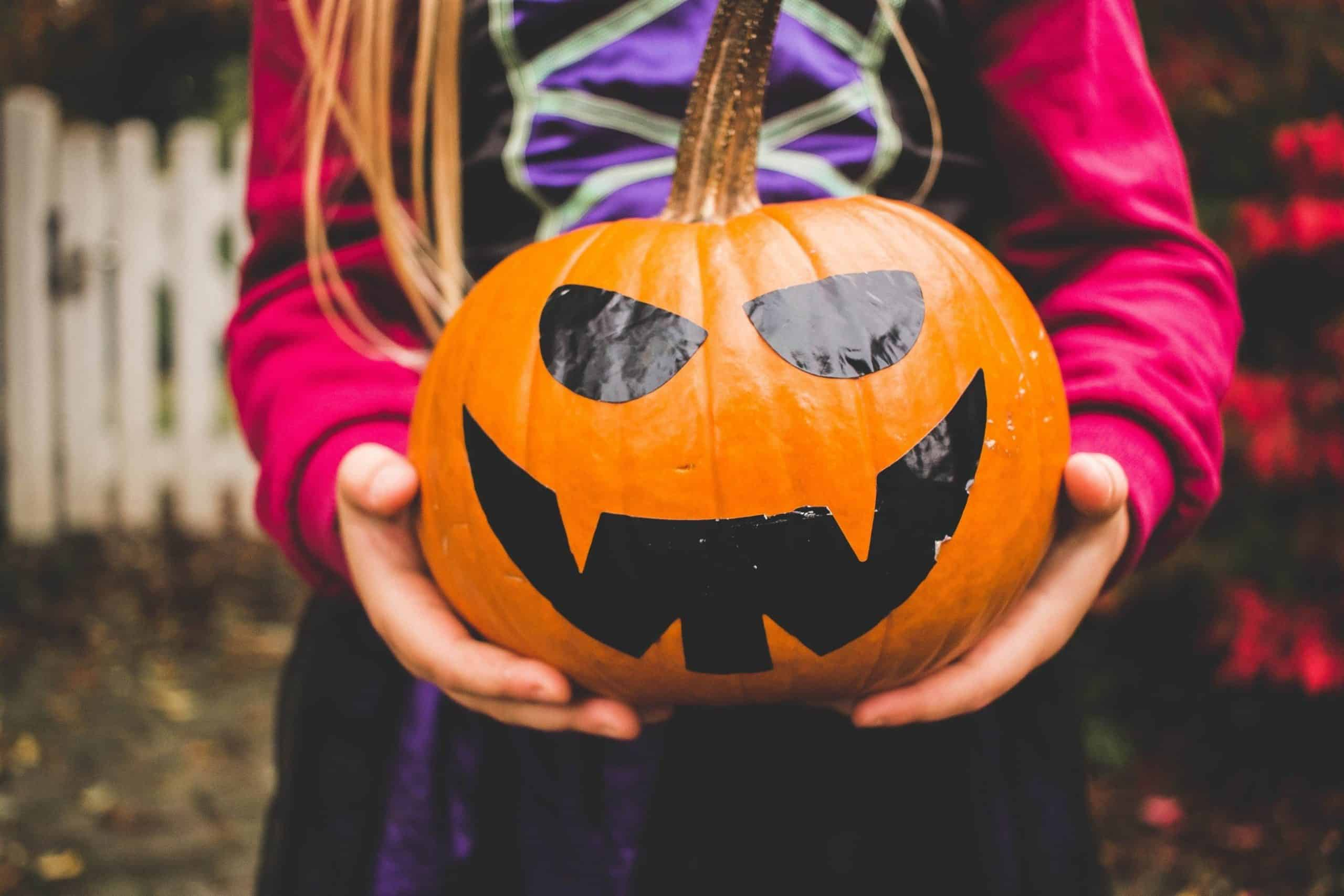 Little Girl Holding Decorated Large Pumpkin Ready For Halloween
