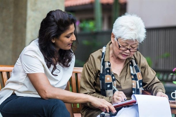 woman sitting outside with family member signing a Will document